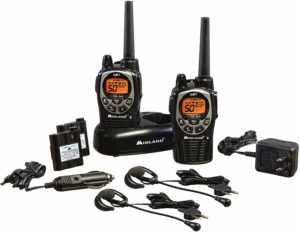 This is an image of 2 black Midland GXT1000VP4 walkie talkies with chargers, headsets and charging docks