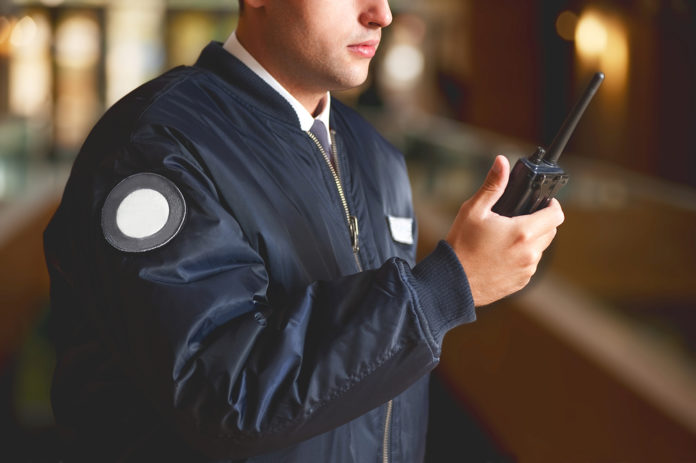 a cut face close up in a security guard with a portable walkie talkie wireless transceiver on a blurry background