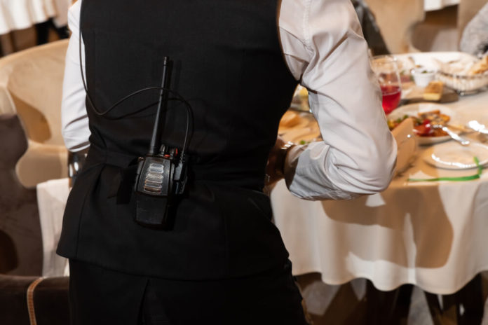 a waiter in a restaurant with a walkie takie radio on his belt