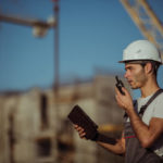 Engineer builder using tablet and walkie talkie, giving instructions at a construction site