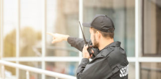 Male security guard using midland portable walkie talkie radio transmitter near building outdoors