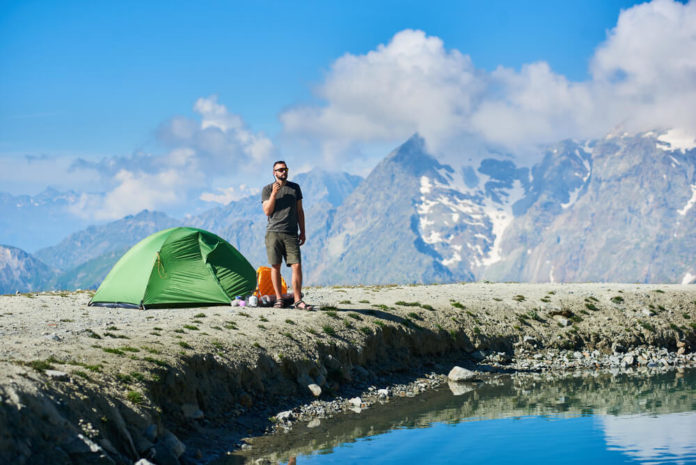 Male traveler holding walkie-talkie while standing by blue lake in mountain valley. Man in shorts and sunglasses talking on radio while resting in mountains. Concept of travelling, hiking and camping.