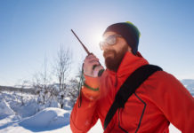 Rescue man talking with portable radio on mountain snow landscape. Back light image.