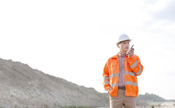 Confident male supervisor using walkie-talkie on construction site against clear sky