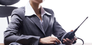 Close-up of businesswoman holding walkie-talkie at work place.