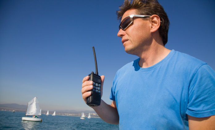 Mature adult man with walk talkie on the background of the sea with sails