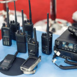 Many portable radio transceivers on table at technology exhibition. Different walkie-talkie radio set. Communication devices choice for military and civil use.