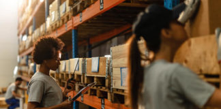worker reading delivery schedule while talking on walkie-talkie in industrial storage compartment.
