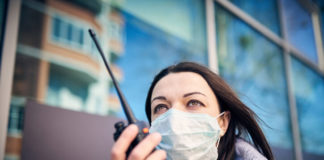 Woman in mask using a walkie talkie on street in the city.