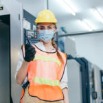 walkie talkie theme. Portrait of engineer woman manager industrial engineer in protective face mask and uniform concern of Coronavirus spreading holding walkie talkie radio phone at industry manufacturing factory